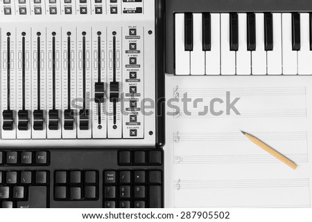 pencil on blank music sheet, studio mixer, piano & keyboard for composer / music production concept background