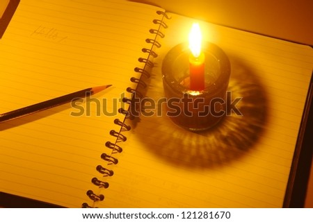 Pencil on notebook with candlelight Open notebook and burning candle on dark