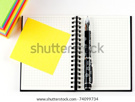 pencil on open note book. Colorful paper notes