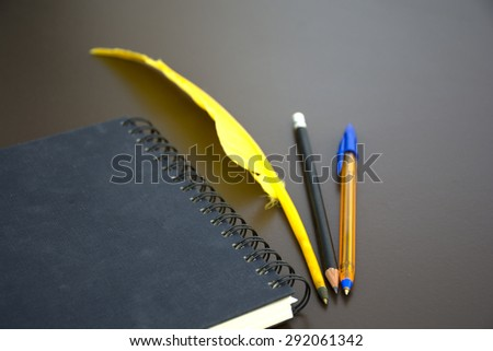 Pencil, pen, quill and book
