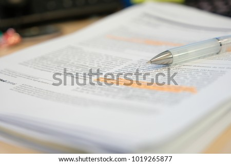 Pencil placed on scientific journal paper with highlight color