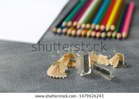 Pencil sharpener and pencil shavings with small particles, white paper and colorful pencils on blackboard background. School supplies. Concept back to school #1479626243