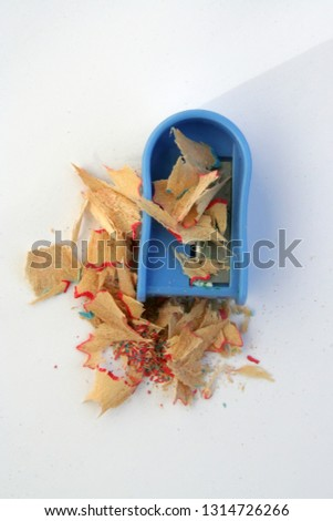 Pencil sharpener and sawdust. Dirty pencil sharpener. Pencil sharpener filled with sawdust.