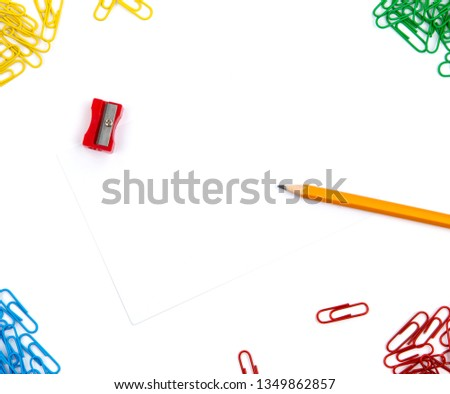 Pencil, sharpener, paper clips lie in different angles of the sheet on a white background. Hero image and copy space
