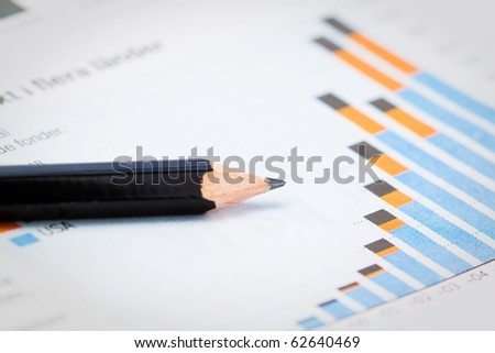 pencil showing a diagram in newspaper with shallow depth of field - stock photo
