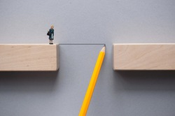 Pencil sketch bridging the gap between wooden blocks for female miniature figure to cross