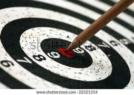 Pencil sticks out in the target for darts