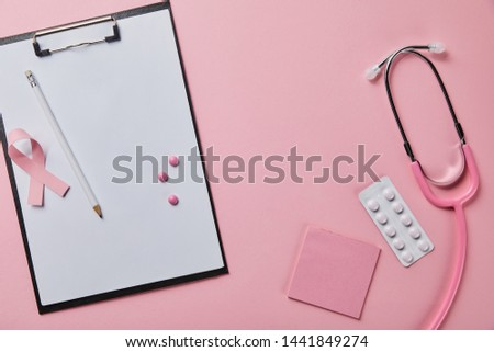 pencil, three pills and breast cancer ribbon on folder with empty paper near stethoscope, blister pack and pice of paper on pink background