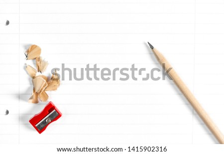 Pencil with sharpening shavings on school book background #1415902316