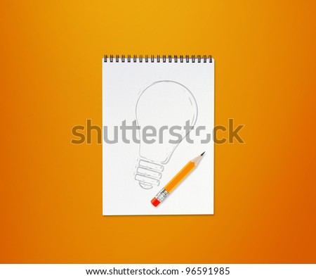pencils and notepad and drawing light bulb on orange background.