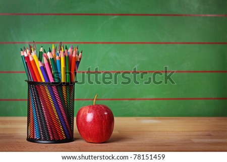 Pencils and red apple on table