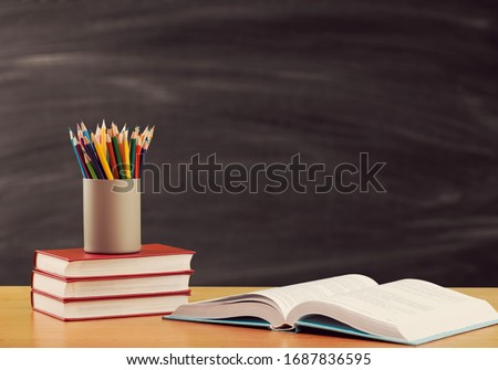 Pencils and study book on the desk on blackboard background