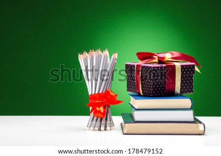Pencils, books and a present against green background