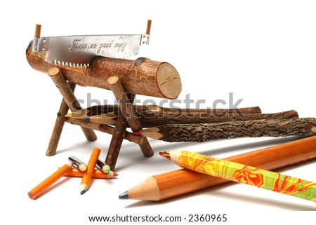Pencils from natural wood of various type and the size near to a saw and a log
