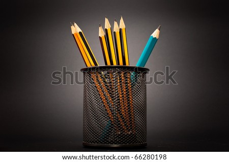 Pencils in a pen holder over a dark background