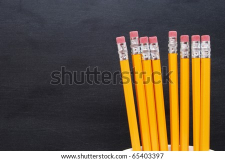 pencils in cup in front of blackboard - stock photo
