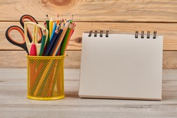 Pencils in metal basket and blank notebook. Set of colored pencils with scissors in metal holder and empty paper notepad. Education concept.