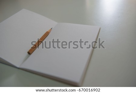 Pencils on the white book on the table . #670016902