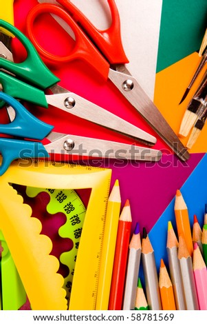 Pencils, scissors, rulers, paintbrushes on cardboard