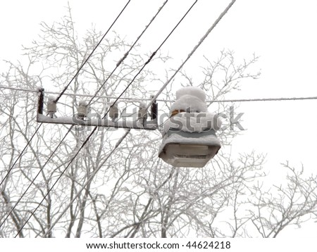 Pendant city lantern on the wires, covered with snow