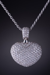 Pendant heart shaped with diamonds in white gold on a gray background with silver and zircons. Macro photo