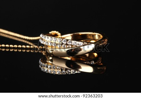 Pendant in form of rings with gem on black