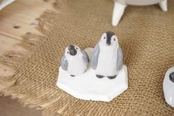 Penguin ceramic. Penguin ceramic miniatures for home decor with soft focus and window light.