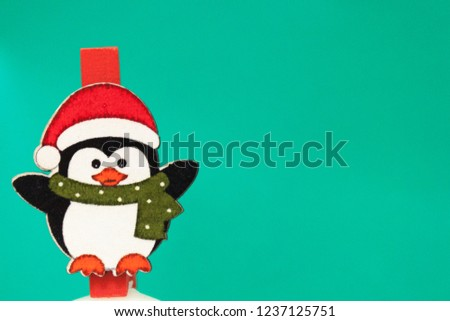 Penguin in a red hat and scarf stands on a green background. Background for new year greeting card. Template for post about Christmas