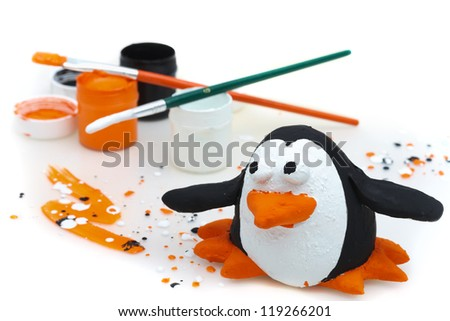 penguin made of salty dough and color paints on a white background