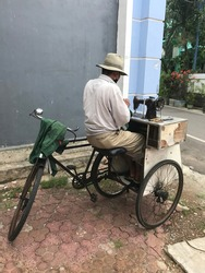 Penjahit keliling is doing the customer's order on his bicycle. Its The itinerant seamstress with three wheel bicycle.