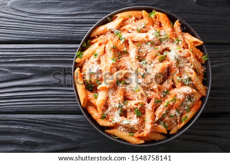Penne alla Vodkais a classic Italian pasta dish made with penne in a creamy tomato and vodka sauce close-up in a plate on the table. Horizontal top view from above ストックフォト ©