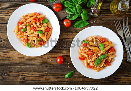 Penne pasta in tomato sauce with chicken, tomatoes, decorated with basil on a wooden table. Italian food. Pasta Bolognese. Top view