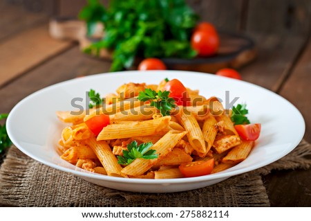 Penne pasta in tomato sauce with chicken, tomatoes decorated with parsley on a wooden background