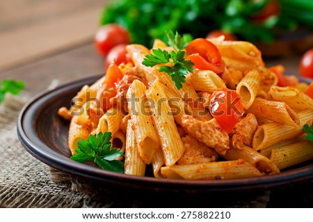 Shutterstock Penne pasta in tomato sauce with chicken, tomatoes decorated with parsley on a wooden table