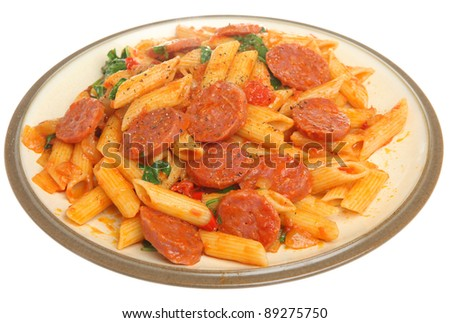 Penne pasta & salami in tomato sauce with wilted arugula.
