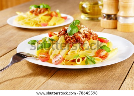 Penne pasta with a bolognese tomato beef sauce on the oak table