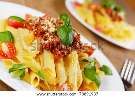 Penne pasta with a tomato bolognese beef sauce in the white plate