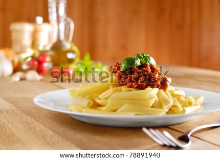 Penne pasta with a tomato bolognese beef sauce on the kitchen table