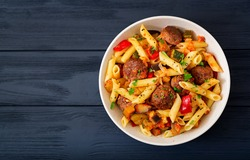 Penne pasta with meatballs in tomato sauce and vegetables in bowl. Top view. Flat lay