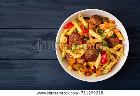 Penne pasta with meatballs in tomato sauce and vegetables in bowl. Top view. Flat lay #711299218