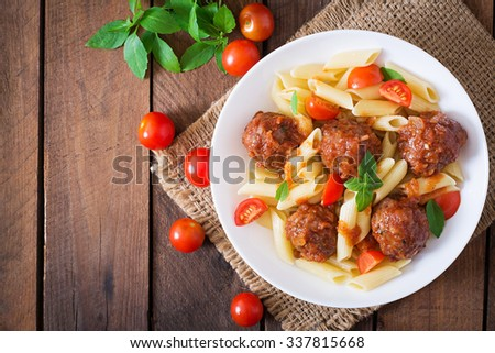Penne pasta with meatballs in tomato sauce in a white bowl. Top view