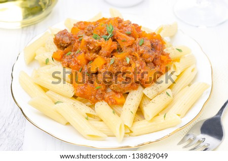 penne pasta with sauce of beef, tomato and pumpkin on a white plate, top view, closeup