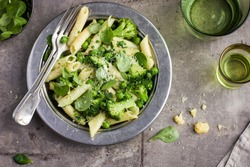 penne  pasta with spinach pesto sauce, green peas and broccoli,  top view