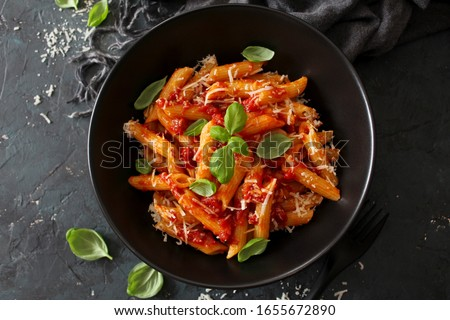 Penne pasta with tomato sauce, parmesan cheese and basil on dark background. Top view with copy space.