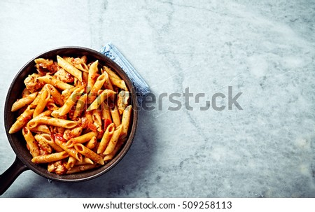 Penne pasta with tomatoes, pepper and chicken breast. Italian pasta. Italian food. Home made food. Concept for a tasty and healthy meal. Gray stone background. Top view. Copy space.