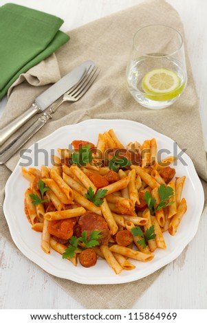 penne with chorizo and sauce on the white plate
