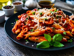 Penne with sausages, tomato sauce, parmesan cheese, basil and vegetables served on wooden table