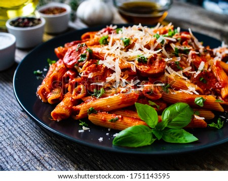 Penne with sausages, tomato sauce, parmesan cheese, basil and vegetables served on wooden table ストックフォト ©