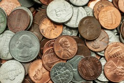 Pennies, nickels, and quarters fill the frame in a close up shot of a pile of random American coins.