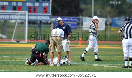 PENNSBURG, PA - SEPTEMBER 24: An unnamed Methacton player (laying down) is tended to by training staff after an injury during the PAC10 conference game against September 24, 2011 in Pennsburg, PA.